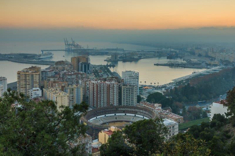 Paesaggio urbano Malaga dal tramonto con l'arena e gli alberi dei tori fotografia stock