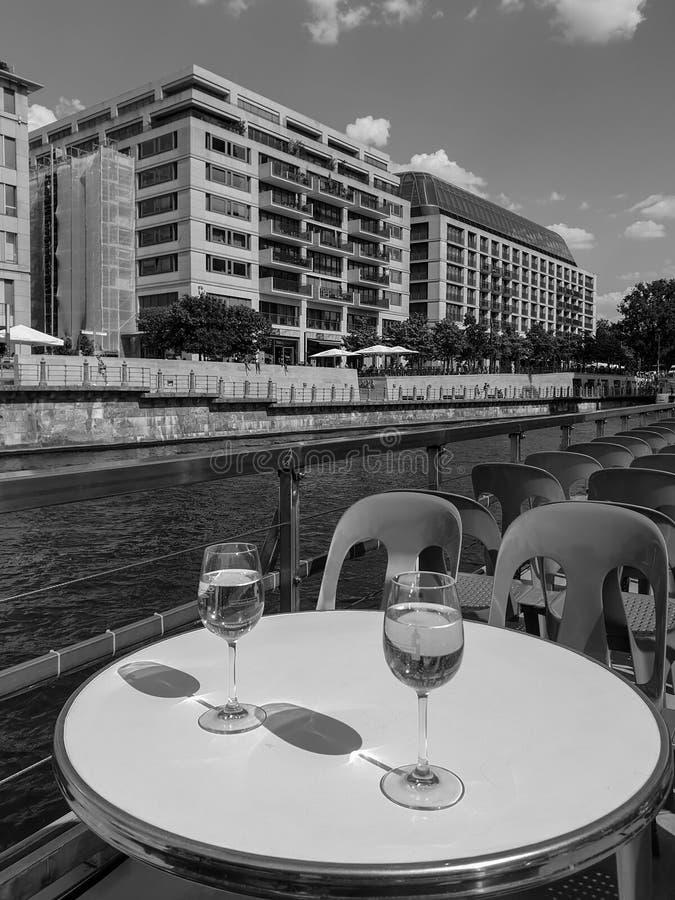 Paesaggio urbano monocromatico con un battello da diporto con due vetri di vino bianco sulla tavola immagini stock libere da diritti