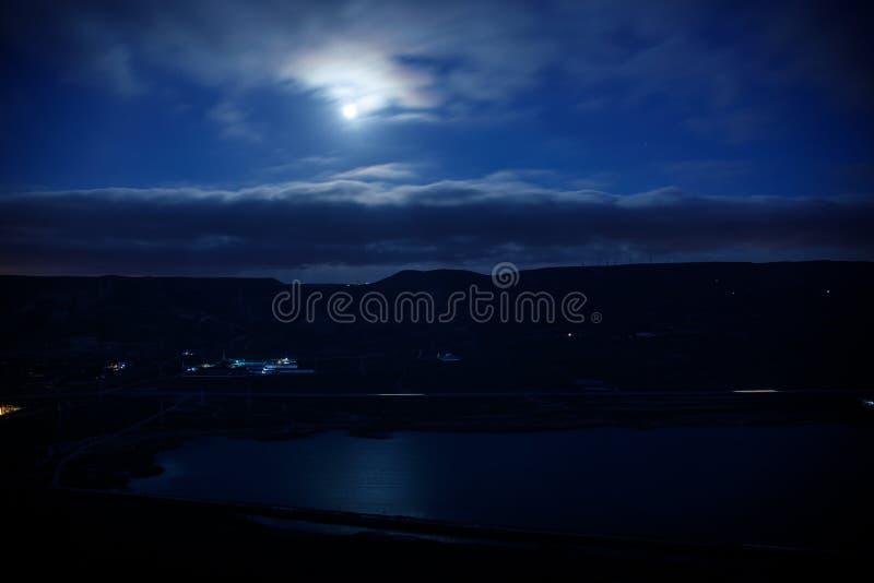 Paesaggio variopinto di notte con il lago, montagne, luna piena, lago Khojasan del cielo blu, Bacu, Azerbaigian Foto panoramica immagini stock