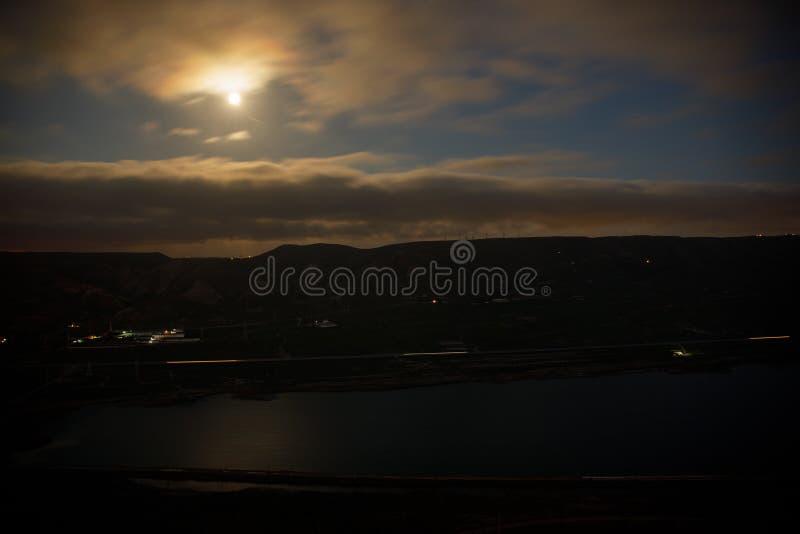 Paesaggio variopinto di notte con il lago, montagne, luna piena, lago Khojasan del cielo blu, Bacu, Azerbaigian Foto panoramica immagine stock