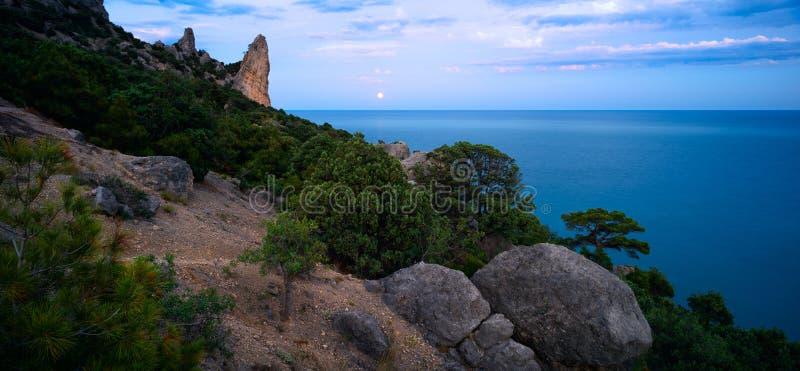Paesaggio variopinto di notte con la luna piena, il percorso lunare e le rocce di estate Paesaggio della montagna al mare immagini stock