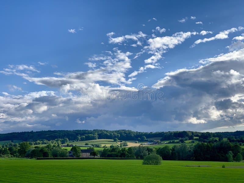Paesaggio verde con le nuvole bianche di un cielo blu fotografia stock