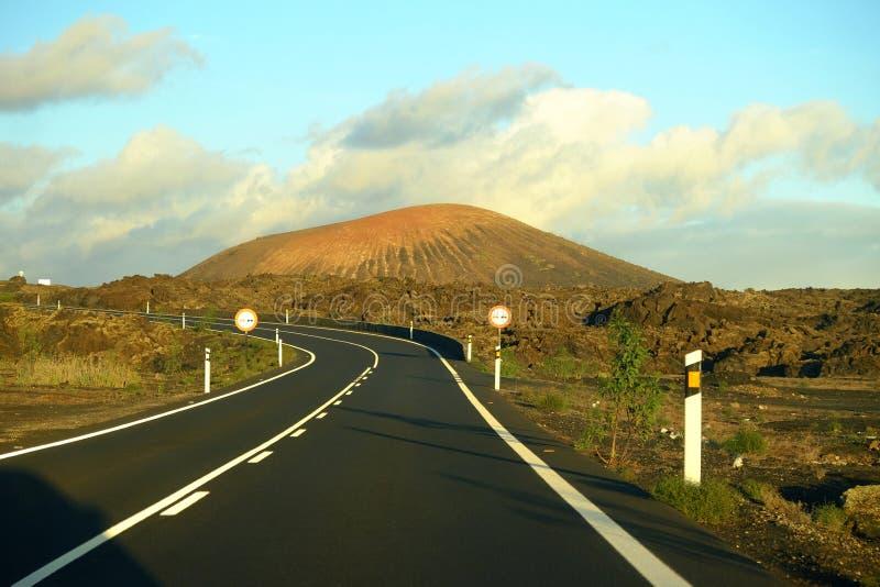 Paesaggio vulcanico e strada curva su Lanzarote, Spagna fotografia stock libera da diritti