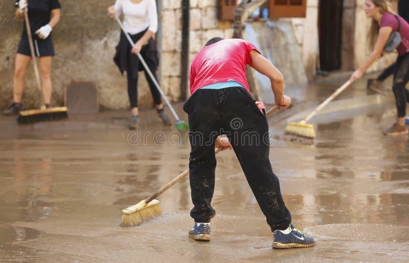 Paesani che puliscono dopo gli inondazioni in San Llorenc in dettaglio di Mallorca dell'isola immagine stock