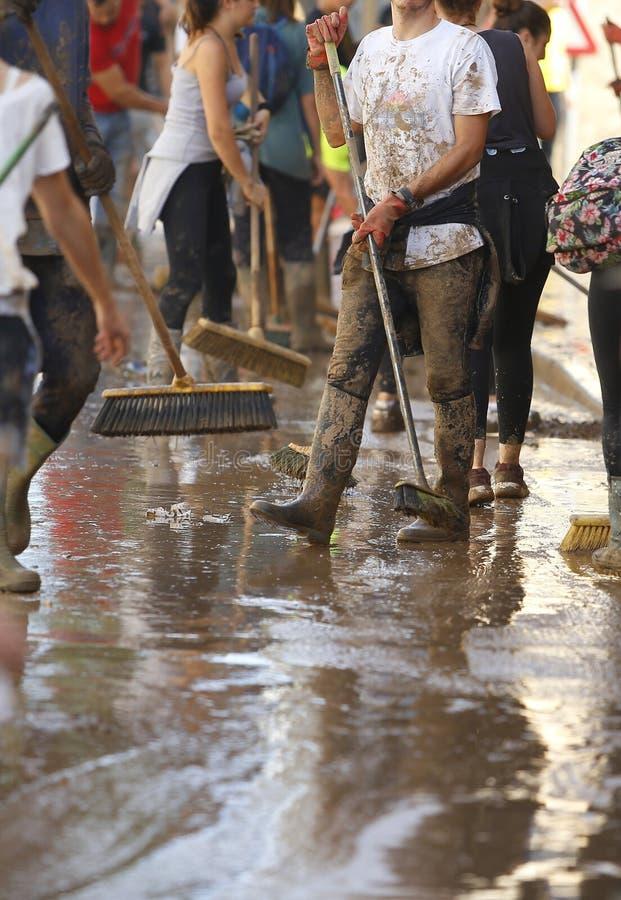 Paesani che puliscono dopo gli inondazioni in San Llorenc nel verticale di Mallorca dell'isola immagine stock