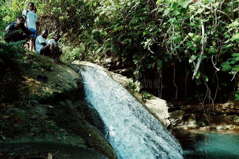 paesani locali che stanno sulla cima di piccola cascata della foresta pluviale della giungla all'isola tropicale a distanza del P immagini stock libere da diritti