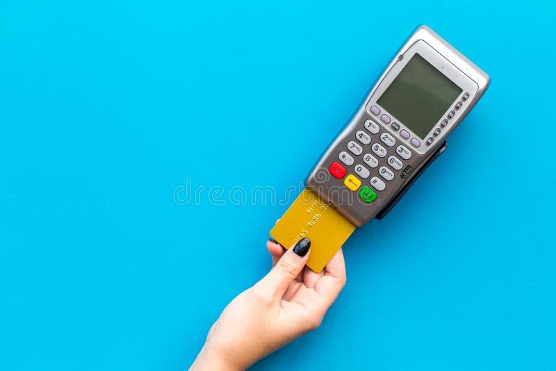 Paga dal terminale di pagamento La mano della donna inserisce la carta di credito al terminale sullo spazio blu della copia di vi immagini stock libere da diritti
