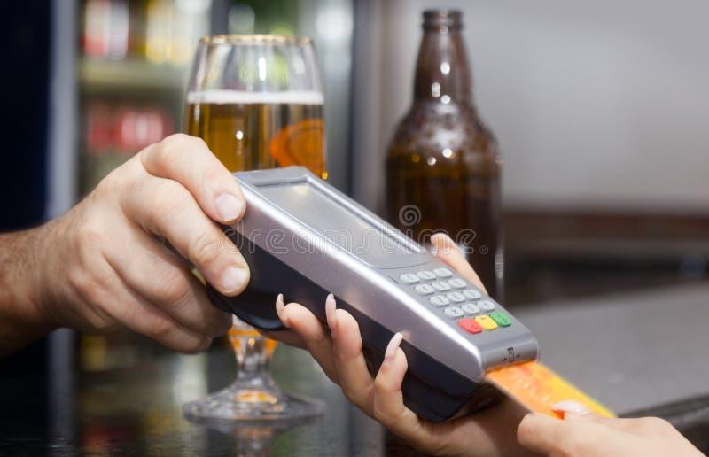Paga de la mujer con la tarjeta de crédito en barra fotos de archivo libres de regalías