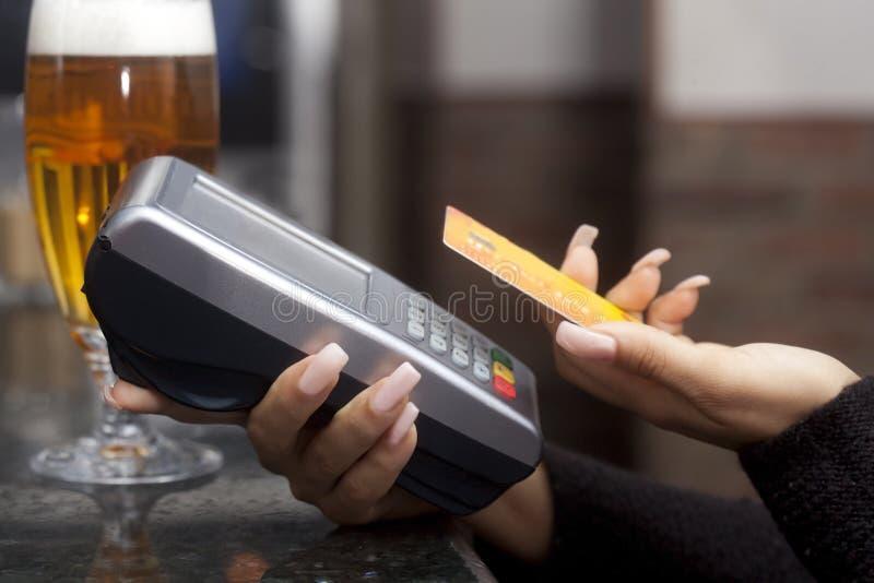Paga de la mujer con la tarjeta de crédito en barra fotos de archivo