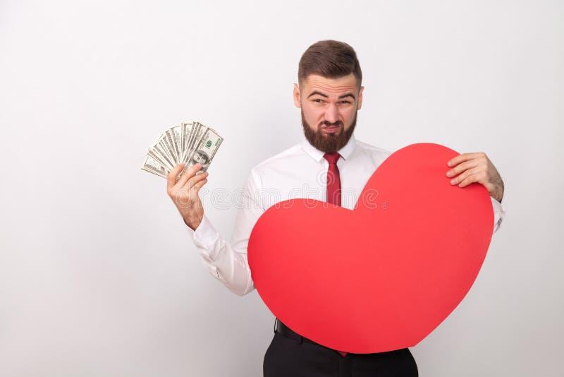 Paga del hombre de negocios para el amor grande, llevando a cabo muchos dólares imagen de archivo