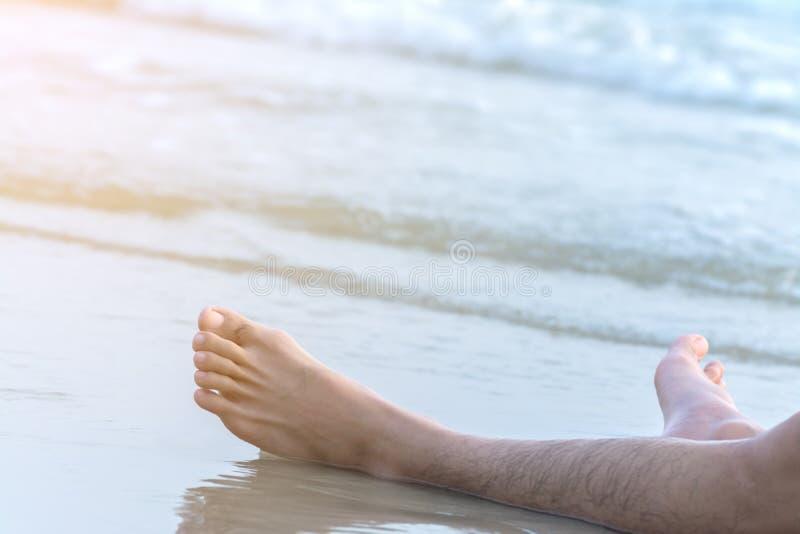 Paga dell'uomo che si rilassa sulla spiaggia immagini stock