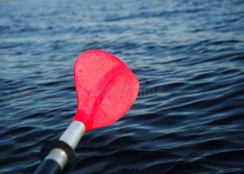Pagaia o remo rossa della barca con il fondo del lago immagini stock