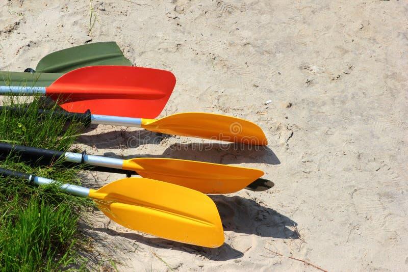 Pagaie variopinte e remi del kajak sulla spiaggia sabbiosa immagine stock