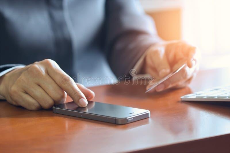 Pagamenti mobili, mani femminili facendo uso dello smartphone e carta di credito per acquisto online fotografie stock