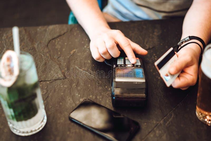 Pagamento con carta di credito al ristorante Codice entrante del perno dell'uomo per l'acquisto di carta di credito fotografie stock