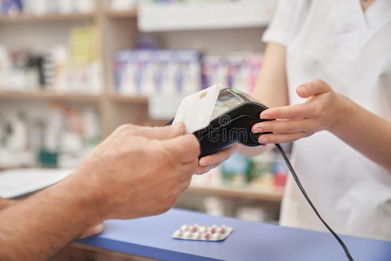 Pagamento con carta di credito per le pillole con il terminale in farmacia immagine stock