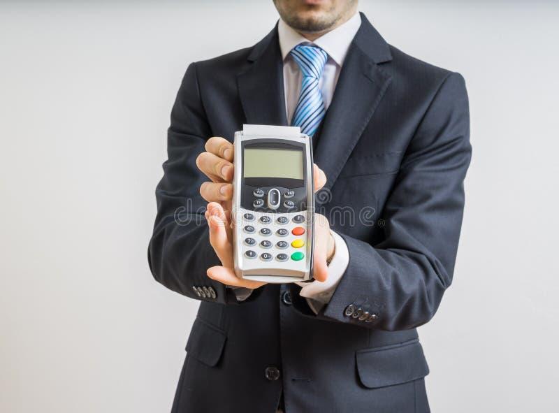 Pagamento con la carta di credito L'uomo d'affari giudica il terminale di pagamento disponibile immagini stock