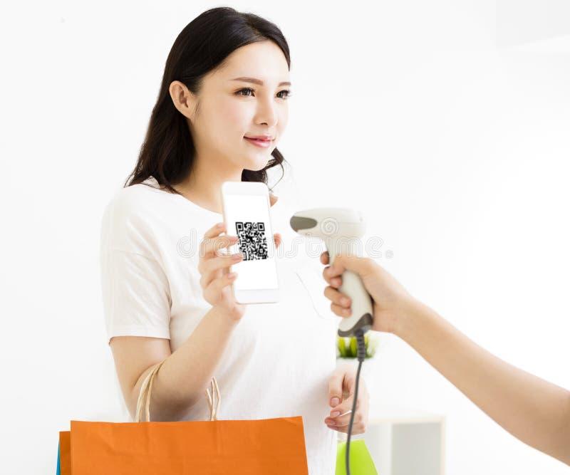 Pagamento da mulher pelo telefone esperto com código do qr fotografia de stock