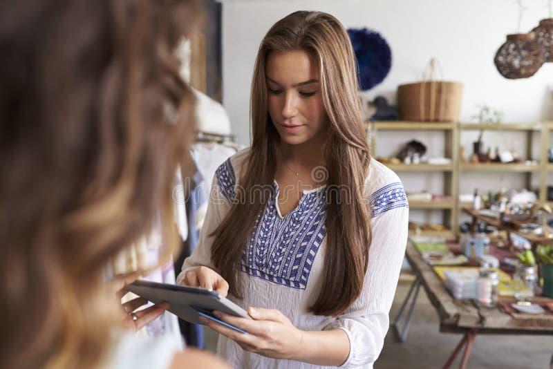 Pagamento de autorização da mulher em um tablet pc em um boutique imagens de stock royalty free