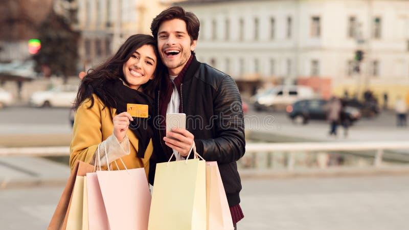 Pagamento ed acquisto online Coppie con la carta di credito e le borse immagine stock
