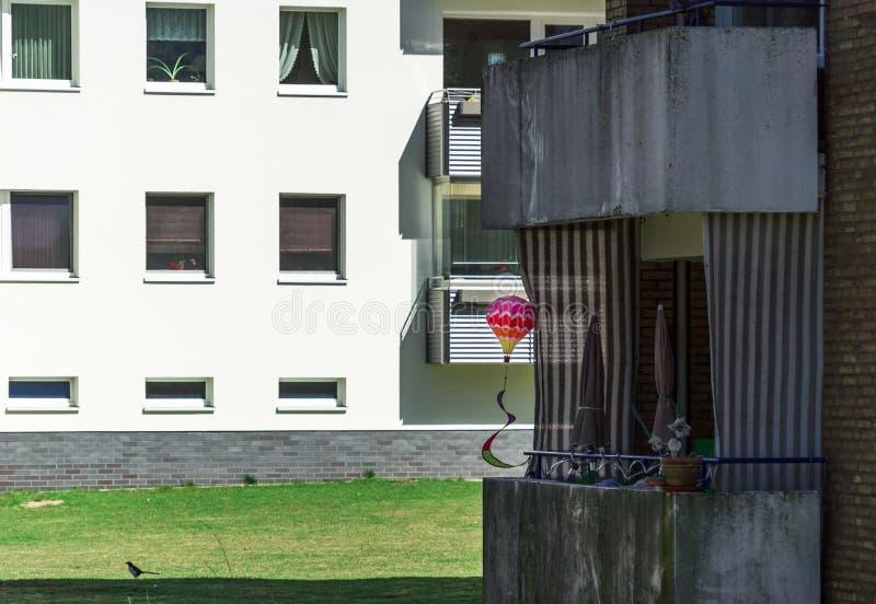 Pagamento escuro obscuro com casas terraced em um subúrbio, com um balão colorido brilhante do brinquedo em um balcão velho sujo  fotos de stock royalty free