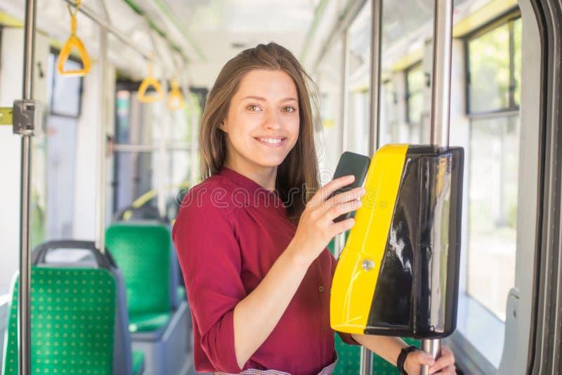 Pagamento femminile della donna conctactless con lo smartphone il trasporto pubblico nel tram fotografie stock libere da diritti