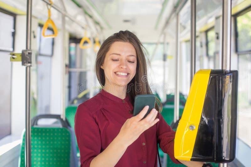 Pagamento femminile della donna conctactless con lo smartphone il trasporto pubblico nel tram fotografia stock libera da diritti