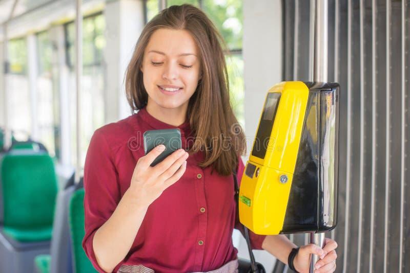 Pagamento femminile della donna conctactless con lo smartphone il trasporto pubblico nel tram immagini stock libere da diritti