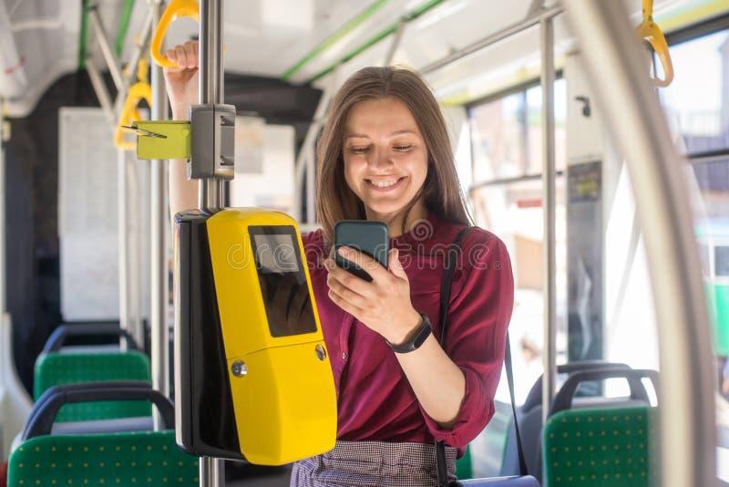 Pagamento femminile della donna conctactless con lo smartphone il trasporto pubblico nel tram immagine stock libera da diritti