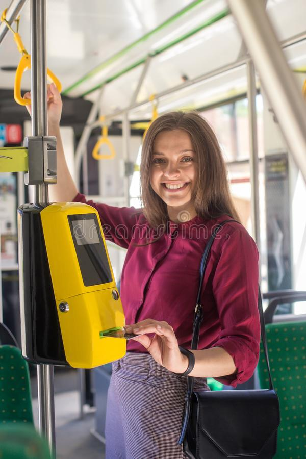 Pagamento femminile della donna conctactless con lo smartphone il trasporto pubblico nel tram fotografie stock