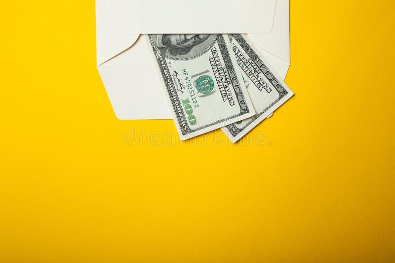 Pagamento nascosto in una busta su un fondo giallo Copi lo spazio immagini stock libere da diritti