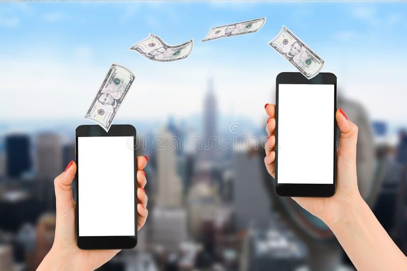 Pagamento o trasferimento di denaro mobile con lo smartphone, l'Empire State Building ed il distretto finanziario come fondo fotografia stock libera da diritti