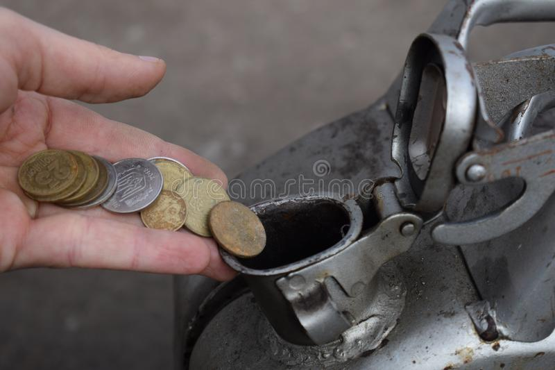Pagamento para o gás, combustível, gasolina, conceito diesel Dinheiro deixando cair da mão, moeda na lata do combustível fotos de stock royalty free