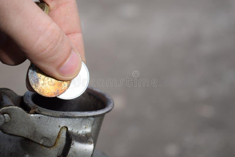 Pagamento para o gás, combustível, gasolina, conceito diesel Dinheiro deixando cair da mão, moeda na lata do combustível foto de stock