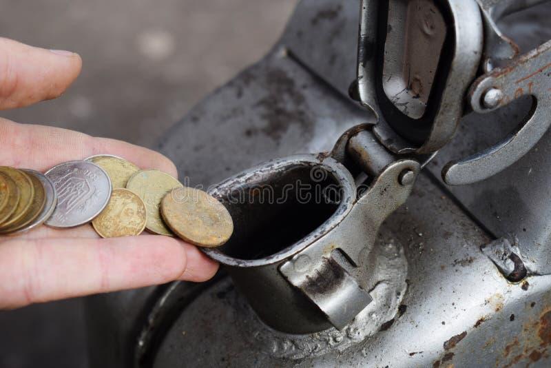Pagamento para o gás, combustível, gasolina, conceito diesel Dinheiro deixando cair da mão, moeda na lata do combustível imagem de stock royalty free