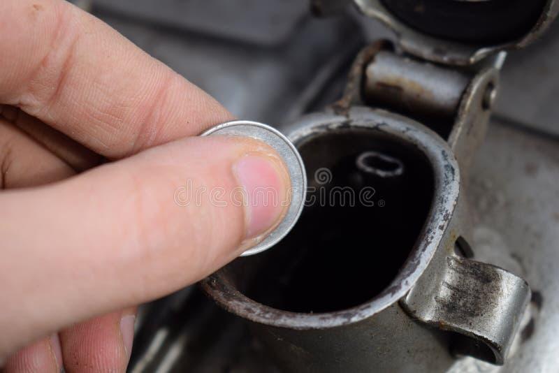 Pagamento para o gás, combustível, gasolina, conceito diesel Dinheiro deixando cair da mão, moeda na lata do combustível foto de stock royalty free
