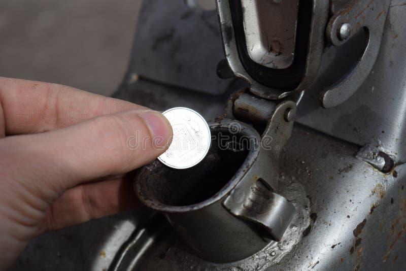 Pagamento para o gás, combustível, gasolina, conceito diesel Dinheiro deixando cair da mão, moeda na lata do combustível fotografia de stock royalty free