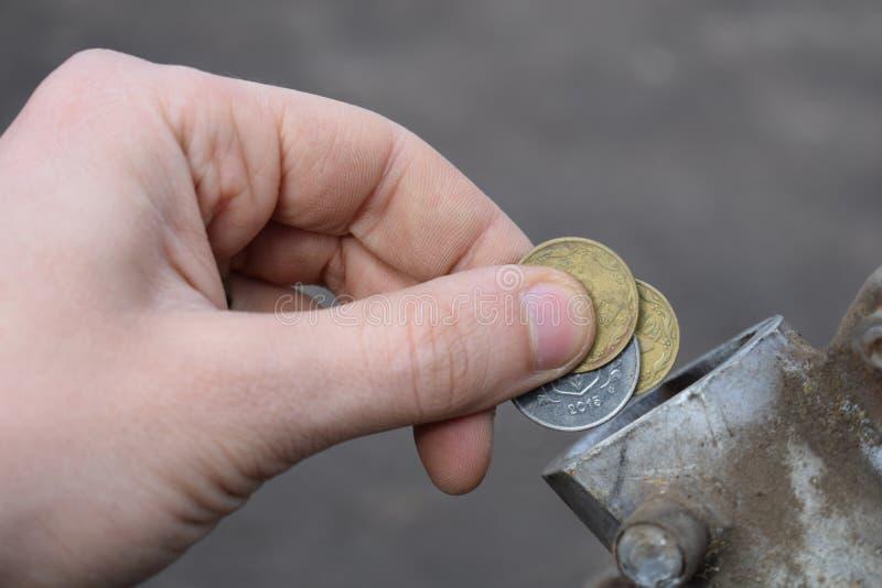 Pagamento para o gás, combustível, gasolina, conceito diesel Dinheiro deixando cair da mão, moeda na lata do combustível imagens de stock