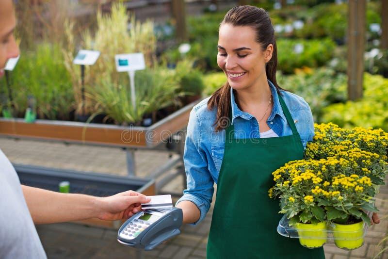 Pagando con la carta di credito al Garden Center immagini stock