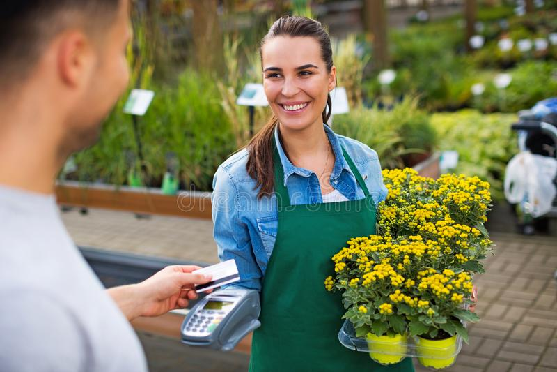 Pagando con la carta di credito al Garden Center immagini stock libere da diritti