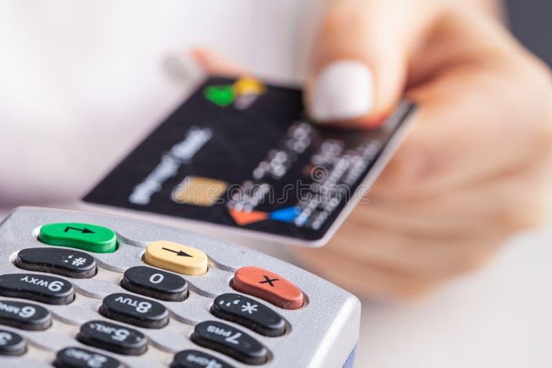 Pagando con la carta di credito Chip card d'inserimento femminile nell'apparecchiatura terminale di pagamento immagine stock libera da diritti