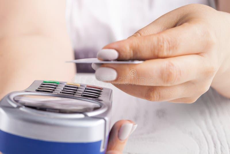 Pagar com cartão de crédito Cartão de microplaqueta de introdução fêmea no dispositivo terminal do pagamento imagens de stock royalty free