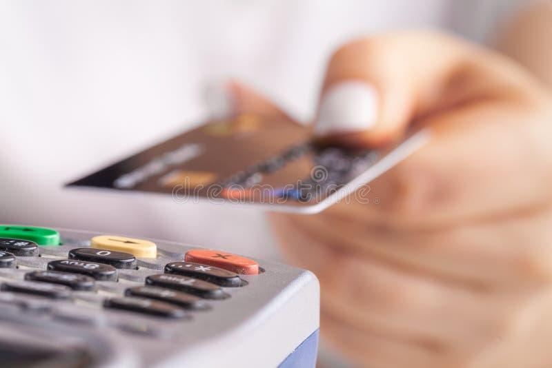 Pagar com cartão de crédito Cartão de microplaqueta de introdução fêmea no dispositivo terminal do pagamento foto de stock