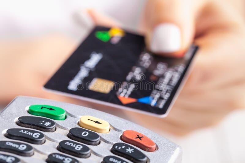 Pagar com cartão de crédito Cartão de microplaqueta de introdução fêmea no dispositivo terminal do pagamento imagens de stock