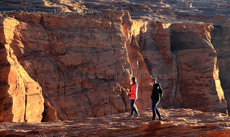 Tourists standing on the edge of the cliffs at Horseshoe bend royalty free stock photos