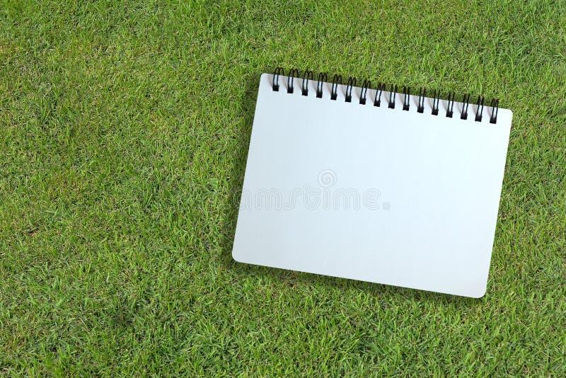 Page blanc de carnet sur la texture d'herbe photo libre de droits