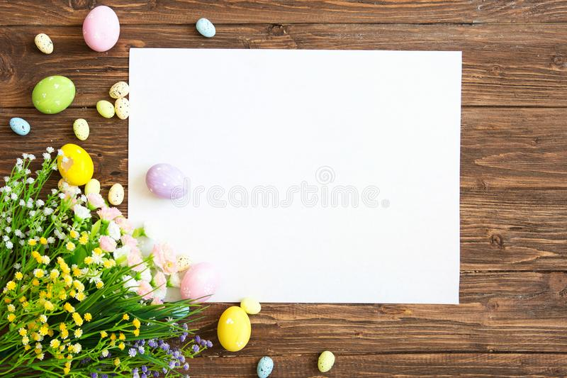 Page blanche avec des décorations de Pâques sur le fond en bois brun Carte de voeux de Pâques photographie stock libre de droits