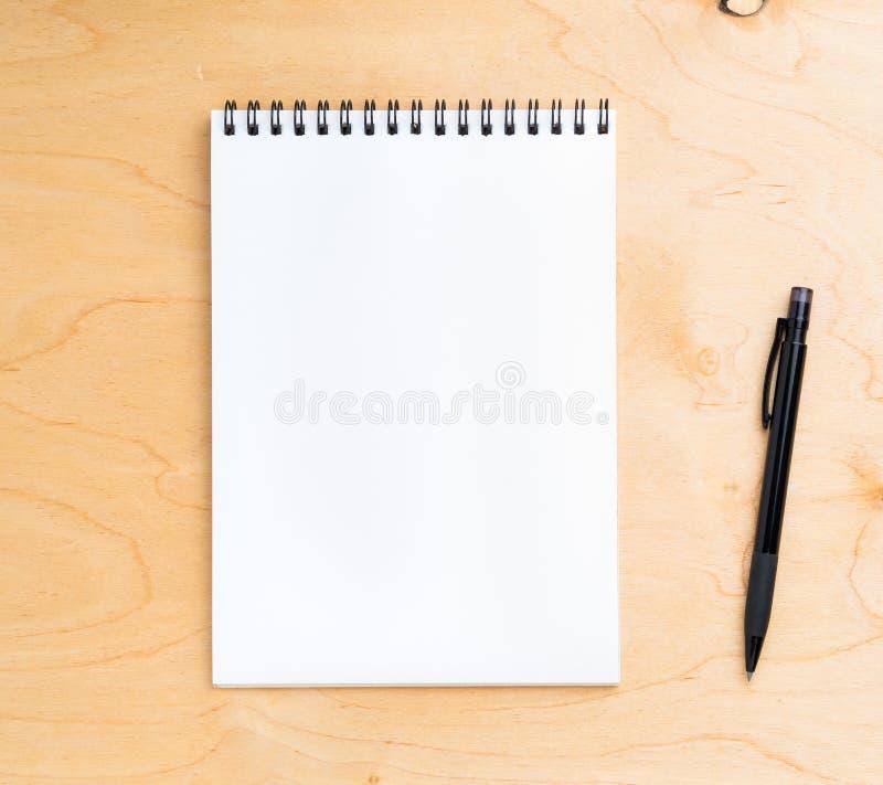 Page blanche de carnet avec une spirale sur un en bois beige neutre images stock