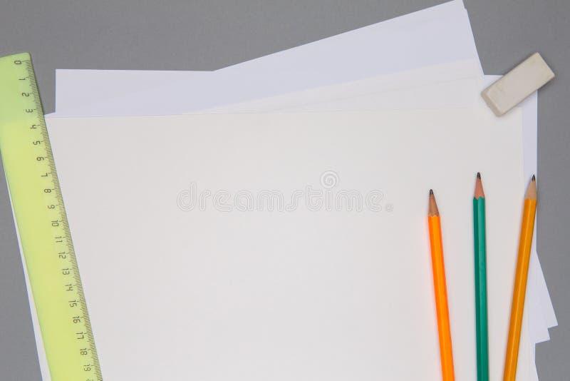 Page blanche de papier, de crayons, de règle et de gomme sur la table grise photographie stock libre de droits