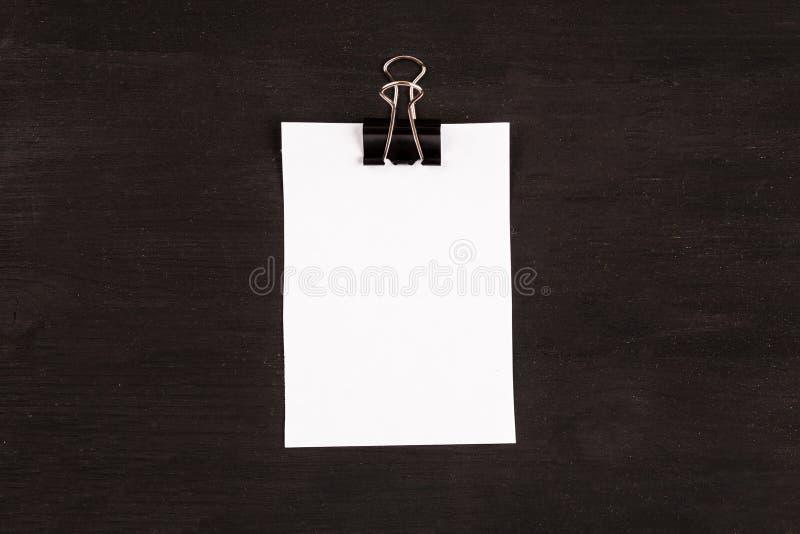 Page blanche du livre blanc avec le trombone sur un fond noir image libre de droits